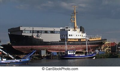 Shipyard with ship in dry dock, large industrial ship + pan...