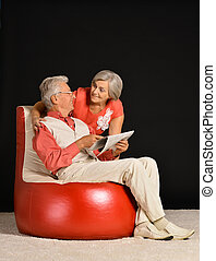 couple reading newspaper - Senior couple reading newspaper...