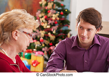 Grandson and grandmother talking during Christmas dinner