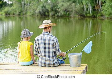Summer fishing - Back view of father and daughter sitting on...
