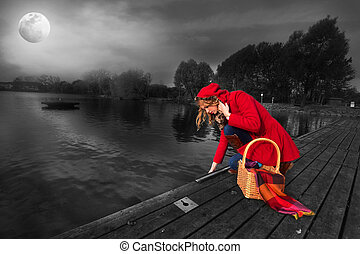 Dark waters - Beautiful girl in a red coat near the pond