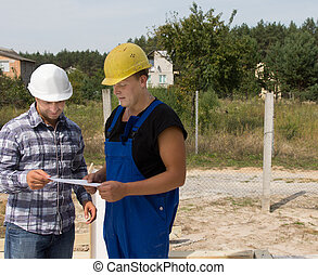Engineer Discussing Project to Construction Worker - Middle...
