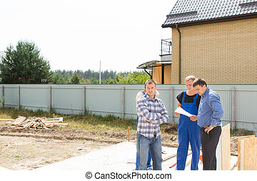 Site engineers discussing details - Group of builders and...