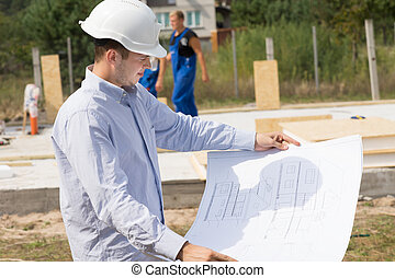 Young architect checking a structural drawing