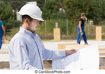 Engineer checking specifications on a plan - Young architect...