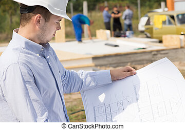 Architect studying a blueprint on site