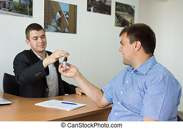 Male Agent Giving House Key to Client - Male Property Agent...