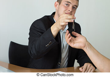 Real Estate Agent Giving House Key to Buyer - Young Male...
