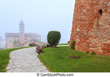 Grinzane Cavour in fog. - Narrow footpath, old brick wall...