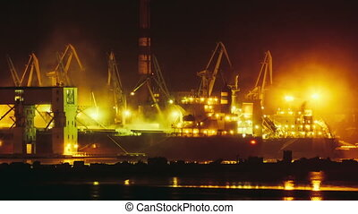 Timelapse of port cranes loading dry-cargo ship at night time