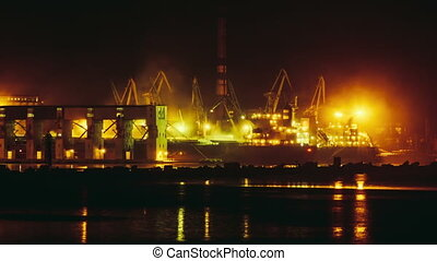 Port cranes loading dry-cargo ship at night timelapse
