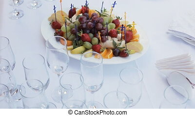 Table layout in a restaurant with fruit canapes and glasses...