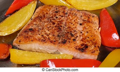 Red fish is fried in a pan with lemon