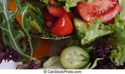 Fresh mixed vegetables falling into bowl of salad isolated...