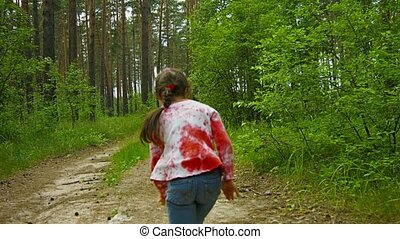 The child is having fun running on the road in a sunny forest