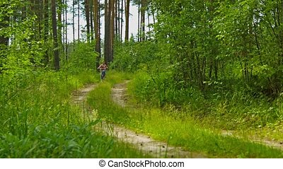 Girl rides through the woods on a bike