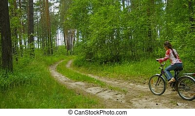 A little girl quickly rides a bicycle on sunny forest