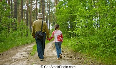 Grandfather walking with granddaughter in summer forest