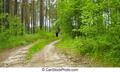 Grandfather walking with granddaughter along the forest road...