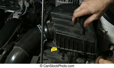 Mechanic Screwing Air Filter - A repairman mounting the air...