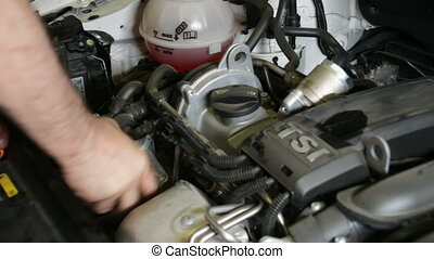 Car Repair Mounting the Oil Filter - A repairman mounts the...