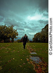 Child walking with dark sky behind - Child walking in...