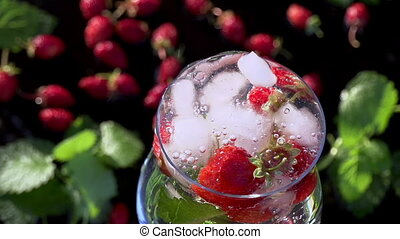 Ice Cubes Falling into Berry Drink - In a glass of clean...