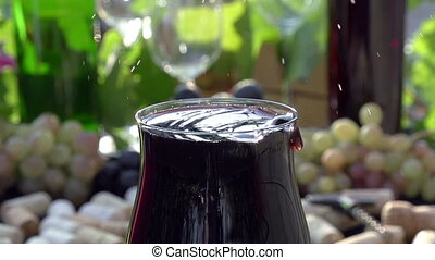 Falling Drops of Red Wine - Glass of red wine close-up on a...