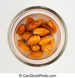 Macro of almonds soaking in water isolated on white -...