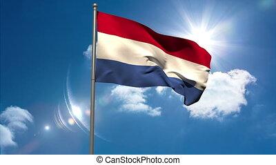 Netherlands national flag waving on flagpole on blue sky...