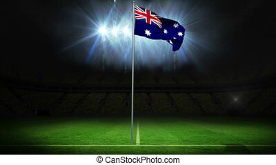 Australia national flag waving on flagpole against football...