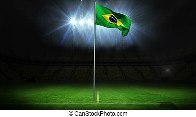 Brazil national flag waving on flagpole against football...