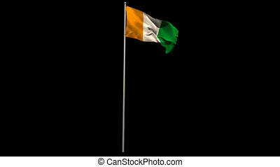 Ivory coast national flag waving on flagpole on black...