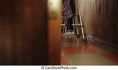 Old woman making efforts in walking around the house with walker