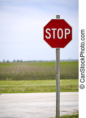 Stop Sign - Stop sign in a rural town in front of a corn...