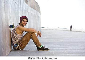 Boardwalk skateboarding - Streetwise youth, sitting carefree...