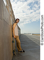 Skateboarder on a Boulevard - Young skater boy leaning...