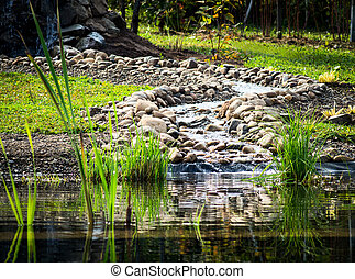 The creek flows into the pond.