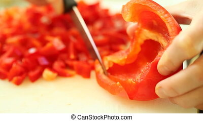 Slicing pepper with kitchen knife - food. hands of woman...