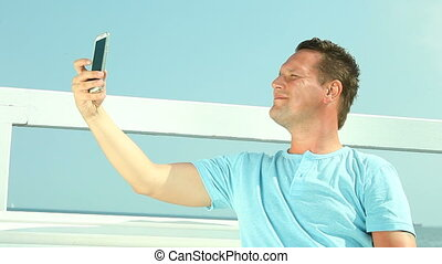 Man taking a selfie by the sea - Man taking photo with...