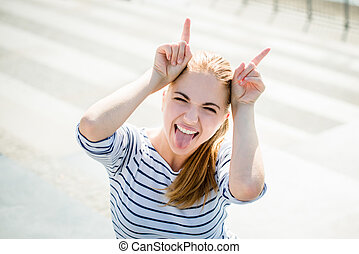 Woman plays devil - Teenager portrait - smiling girl has fun...