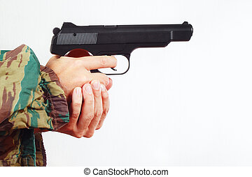 Hands in camouflage uniform with automatic army handgun on...