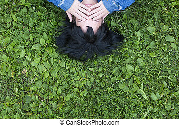 Brunette girl lying on the grass closing his eyes his hands, top view with space for text.