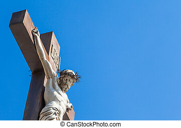 Crucifix made of marble with blue sky in background France,...