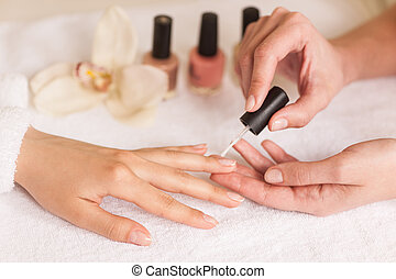 Beautiful girl manicurist doing manicure for woman in beauty...