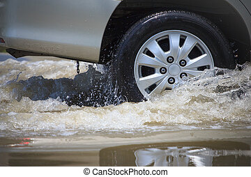 Splash by a car as it goes through flood water