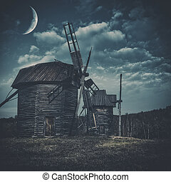 Spooky landscape with few haunted wind mills against dark...
