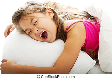 Young girl yawning while waking up