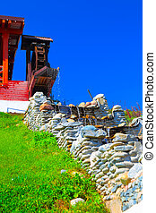 Old syle house with water mill on the blue sky background