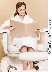 Young woman receiving pedicure in hairdressing salon. Woman...